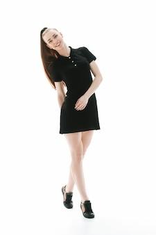 カメラを見て短い小さなドレスを着たエレガントな若い女性。白い背景で隔離。