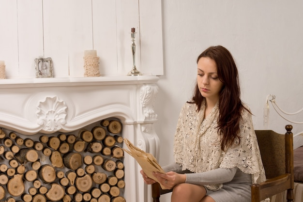 안락의 자에서 독서 앉아 세련 된 옷에 우아한 젊은 여자