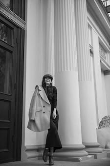 Элегантная молодая женщина смеется, одетая в длинное платье и пальто на плече и шляпу, позирует возле здания, в прохладный день.