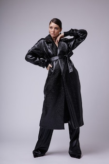 Elegant young woman in leather coat pants accessories on white background gathered dark hair