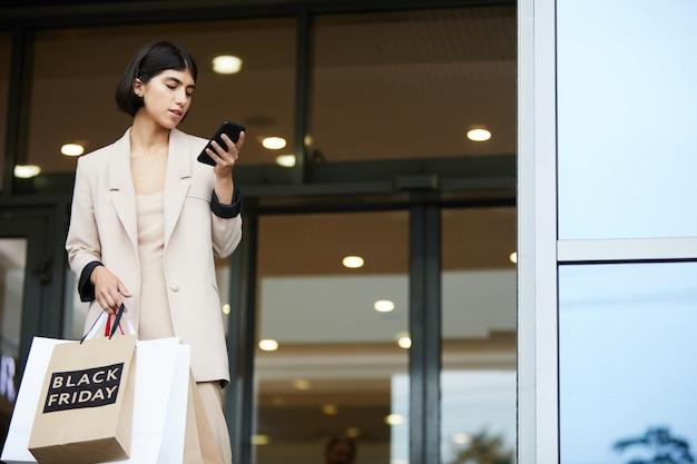 Элегантная молодая женщина покидает бутик
