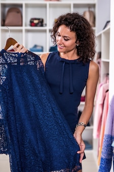 Элегантная молодая женщина ищет новое платье в магазине одежды