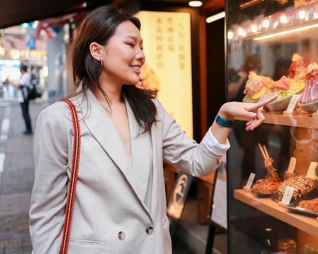 Элегантная молодая женщина, указывая на сладости
