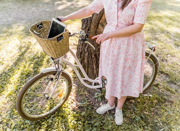 Элегантная молодая женщина позирует с велосипедом