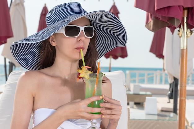 トレンディなつばの広い日よけ帽とサングラスでビーチフロントでリラックスしながら、氷のように冷たいフルーツカクテルをすすりながらエレガントな若い女性