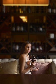 Elegant young woman sitting in restaurant and having good time alone.