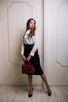 Elegant young woman in skirt and blouse with handbag in room