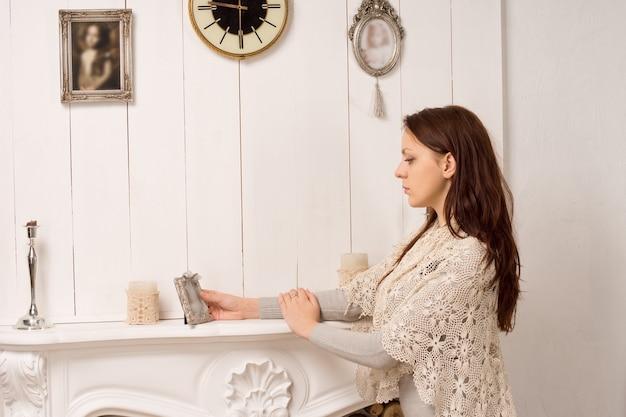 대리석 벽난로에 쉬고 그녀의 팔으로 서 우아한 젊은 여자