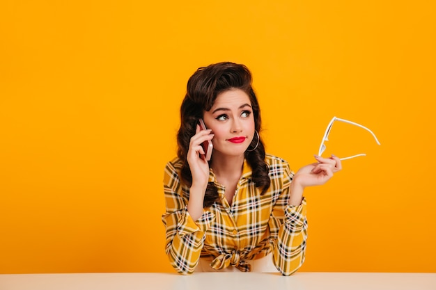 Элегантная молодая женщина разговаривает по телефону на желтом фоне. студия сняла чудесную девушку кинозвезды, держащую очки.