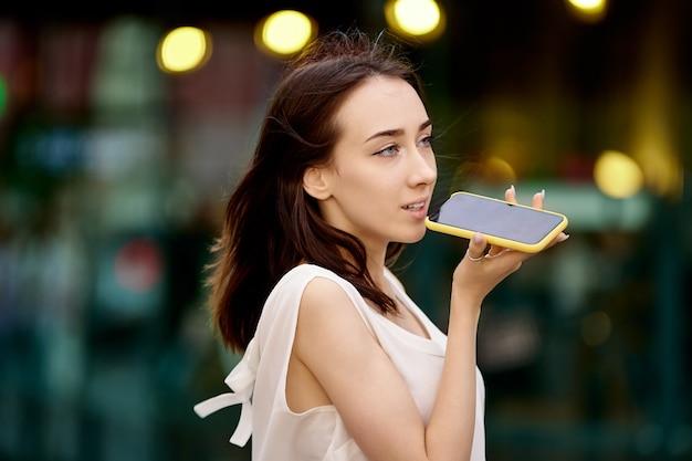 우아한 젊은 여성이 걷는 동안 전화로 이야기합니다.