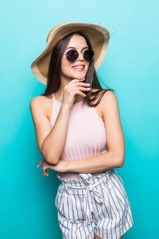 夏休みを考えて、夏のドレス、麦わら帽子、サングラスを身に着けているエレガントな若い女性。パステルブルーの壁に分離されたあごに手を持っている女性の側面図。