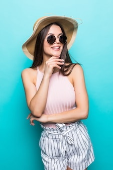 Elegant young woman wearing summer dress, straw hat and sunglasses, thinking about her summer vacation. side view of woman with hand on chin, isolated over pastel blue wall..