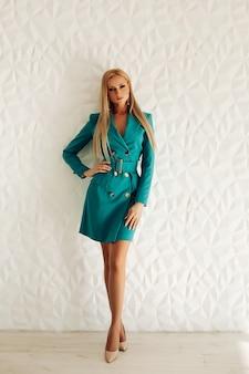 Элегантная молодая женщина со светлыми волосами в стильном платье позирует