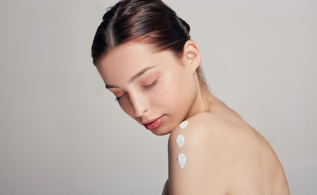 An elegant young woman with brown hair, closed eyes and clean radiant skin sits half-sided on a light. cream on the shoulder. body cream. salon therapy.