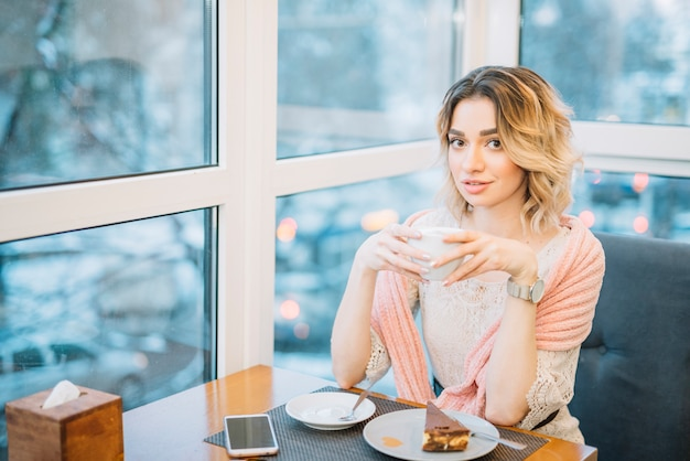 Elegant young woman with cup of drink near smartphone and dessert at table in cafe