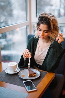 Elegant young woman with dessert and cup of drink near smartphone at table