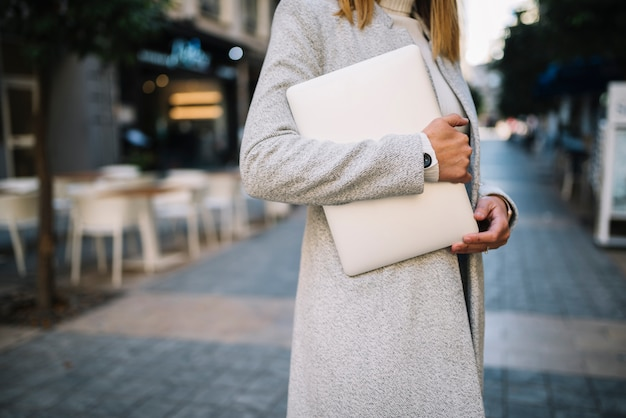 Elegant young woman with laptop on street
