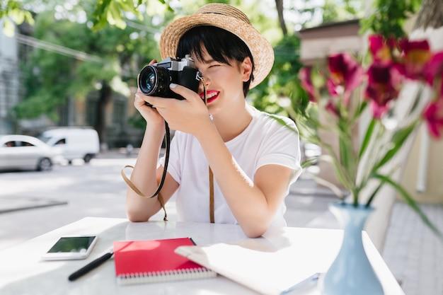 短い黒髪のエレガントな若い女性が写真を保持するプロ