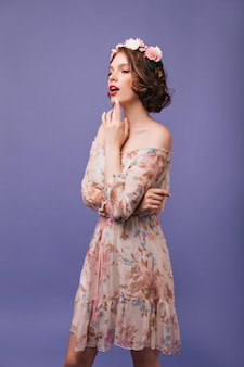 Elegant young woman with short haircut posing with flowers on her head. indoor portrait of fashionable girl in stylish summer dress.