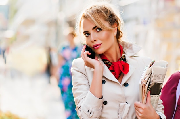Elegant young woman with sparkle make-up talking with someone on phone during walk to office