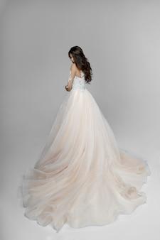 Элегантно очаровательная молодая брюнетка модель в свадебном платье позирует спиной в студии, изолированной на белом пространстве.