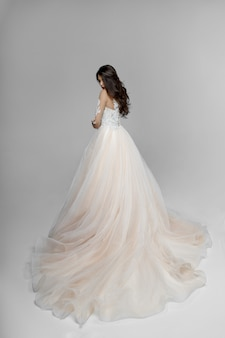 Elegantly charming young brunette model in a wedding dress, poses with back in studio, isolated on a white space.
