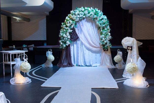 Elegantly styled unique wedding arrangements in empty dimly lit room with flowers on arch