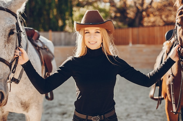 牧場で馬を持つ優雅な女の子