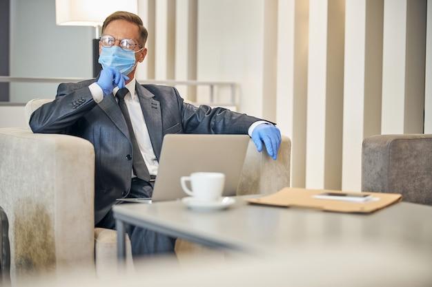 비행 전에 노트북을 사용하고 커피를 마시는 동안 보호 장갑과 마스크를 착용한 우아한 성숙한 남자