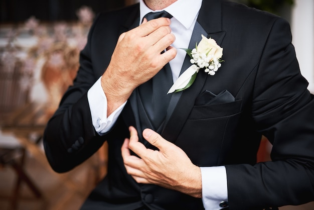 Элегнат жених в черном стильном костюме надевает галстук утром перед свадьбой.