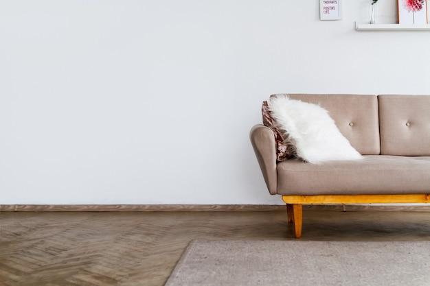 흰 벽 배경에 흰색 푹신한 베개가 달린 세련된 베이지 색 소파의 요소