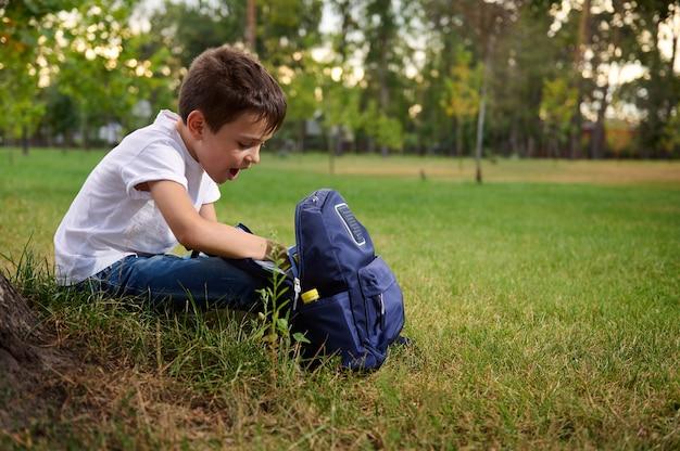 学校での初日の後、緑の芝生の上で休んでいるカジュアルなデニムの小学生の男子生徒。美しい晴れた日のレクリエーション中にランドセルを持つ愛らしい子供。学校に戻るコンセプト