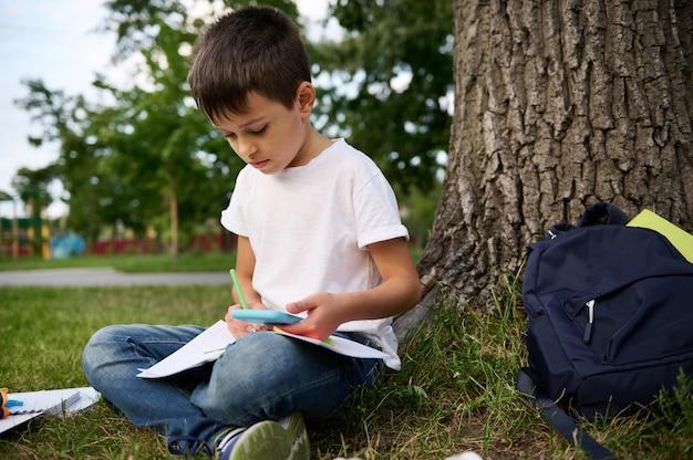 Школьник младших классов сконцентрирован, сосредоточен на решении школьных задач, сидит рядом с деревом на зеленой траве и держит мобильный телефон, делает заметки, пишет в учебной тетради. назад к школьным концепциям