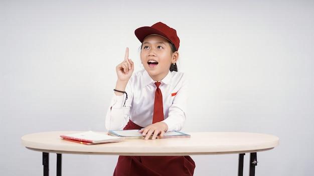 小学校のアジアの女の子は、白い背景で隔離の素晴らしいアイデアを見つけます