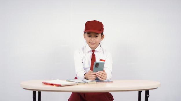 スマートフォンでアイデアを探すことを学ぶ小学校アジアの女の子は、白い背景で隔離をお楽しみください