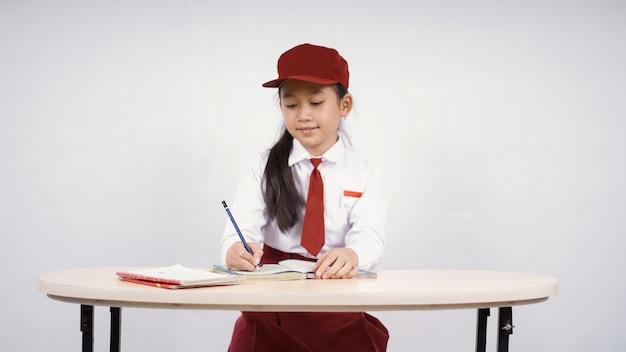 흰색 배경에 고립 된 쓰기를 배우는 초등학교 아시아 소녀