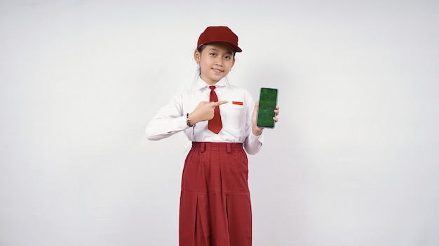 Elementary school asian girl pointing at smartphone screen isolated on white background