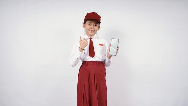 스마트폰 화면을 보여주는 초등학교 아시아 소녀와 흰색 배경에 격리된 괜찮아