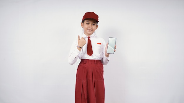 Elementary school asian girl showing smartphone screen and okay isolated on white background