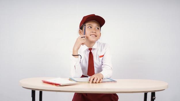 흰색 배경에 격리된 글을 쓸 생각을 하는 초등학교 아시아 소녀