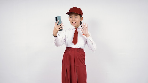 Elementary school asian girl waving at her phone screen isolated on white background