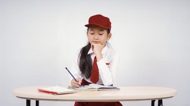 Elementary school asian girl writing enjoying isolated on white background