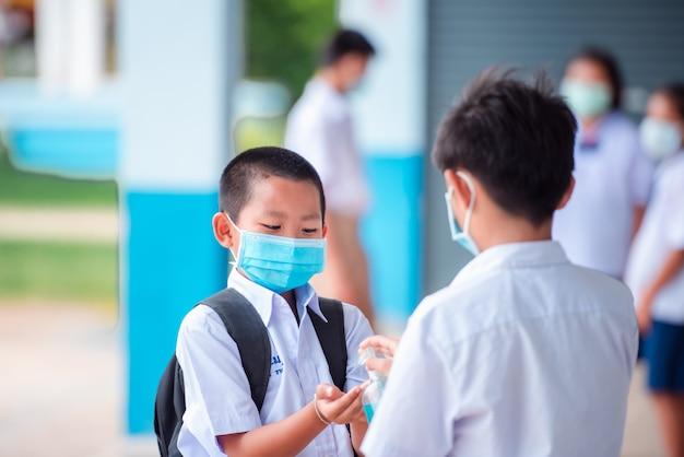 小学校のアジアの学生はコロナウイルス感染を防ぐために医療マスクを着用します