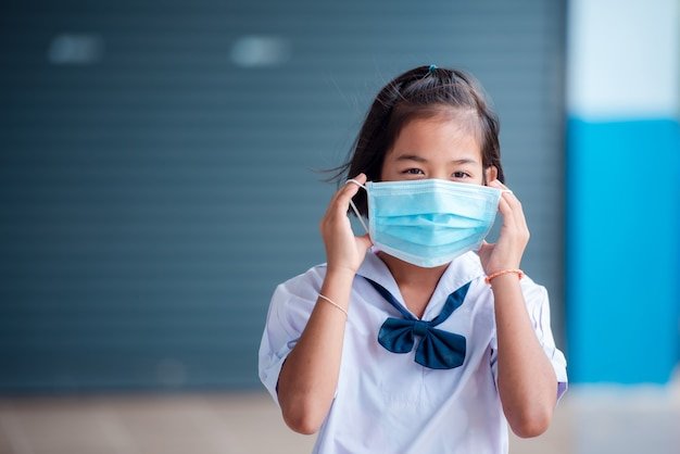 Elementary school asian students wear a medical mask to prevent coronavirus