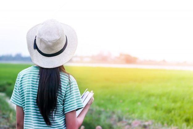 Elementary school children wear a hat on the back and hold a book in the vast green pasture.