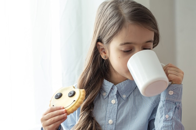 An elementary school girl is having breakfast with milk and funny cookies in the form of a smiley.