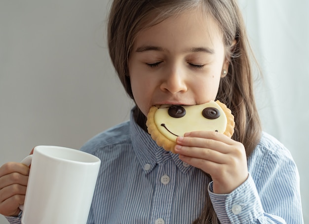 An elementary school girl is having breakfast with milk and funny cookies in the form of a smiley