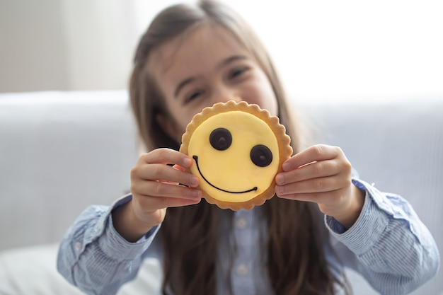 An elementary school girl in a shirt holds a bright yellow smiley cookie on a blurred background.