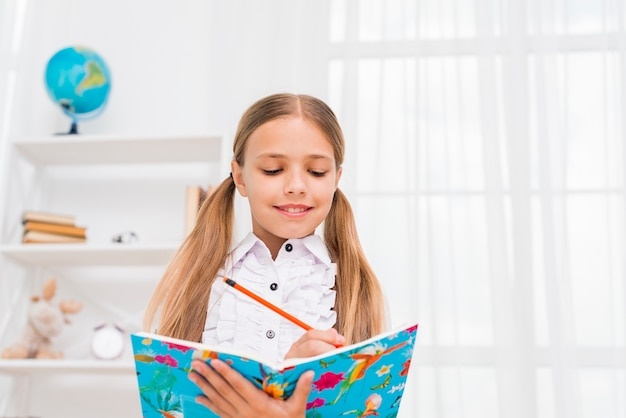 Elementary school girl standing doing homework