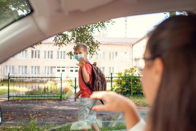 Ученик начальной школы идет в школу утром в защитной маске